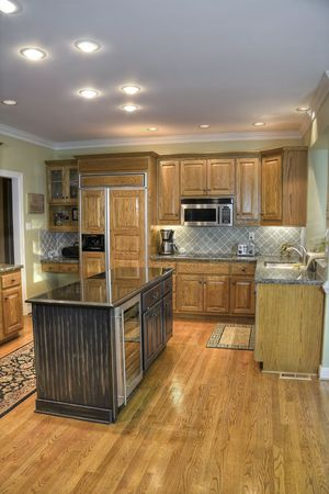 Luxury modern kitech with wooden cabinets and hardwood flooring.