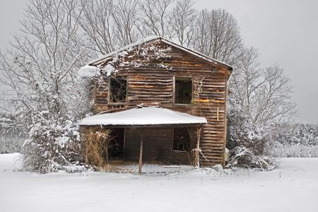Snow covered old abandoned house in the middle of a field.
