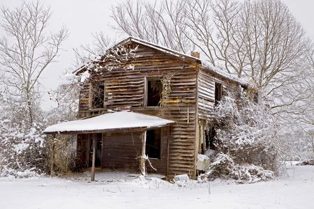 Snow coverd old abandoned house sitting in the middle of a field.