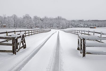 Snow covered countryside driveway with wooden fencing.