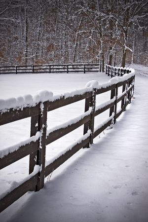 Snow covered wooden fence line that borders a field.