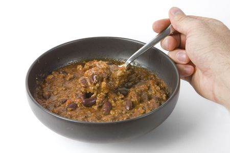 Hand holding a spoon into a bowl of chilli isolated over a white background. photo