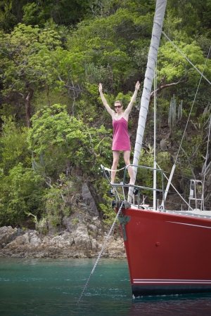 Young women standing on the front of a luxurious sailboat in the tropics. Stock Photo - 6043234