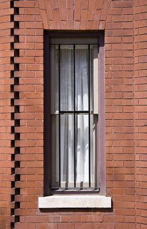 Close up detail of a brick homes window with security bars. photo