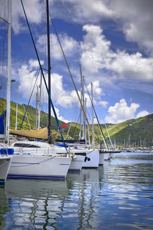 Beautiful tropical harbor lined with sailboat yachts and lush mountains in the background. Stock Photo