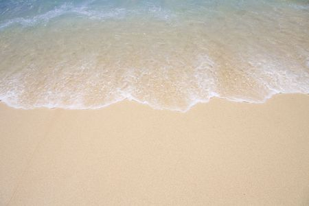 Background of tropical beach shoreline as wave runs up the sand.