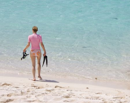 Young woman walking into tropical water to go snorkeling. photo