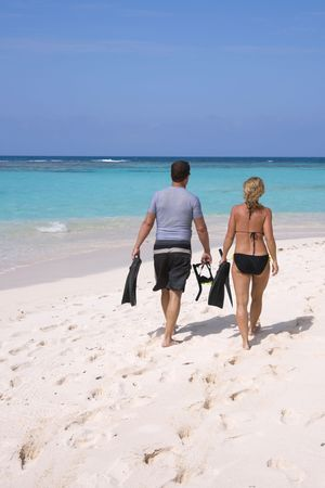 A couple walking towards tropical water to go snorkeling. photo