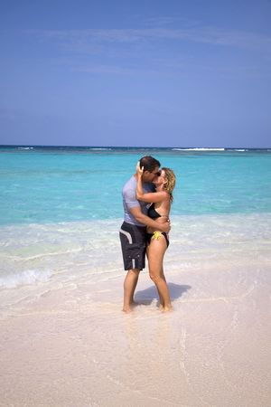 romance: A couple on vacation kissing on a beautiful tropical shoreline. Stock Photo