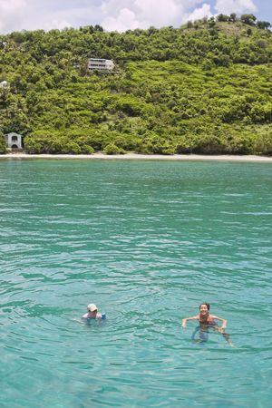 Two young women swimming in beautiful clear tropical water. photo