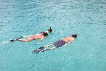 Family on vacation snorkeling in beautiful and clear tropical water. photo