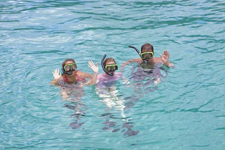 Family on vacation snorkeling in the tropics. photo