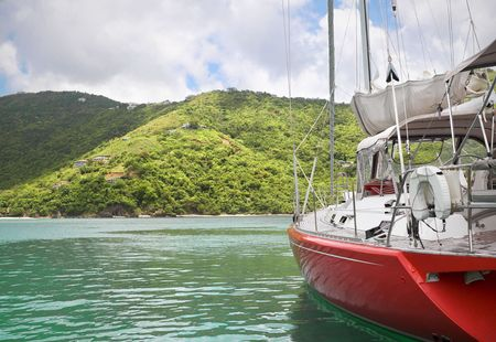 Beautiful large and luxurious sailboat anchored next to a tropical island. photo