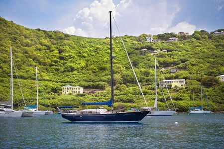 Large and luxurious sailboats anchored infront of beautiful tropical island. photo