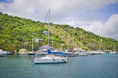 Large and luxurious sailboats anchored next to a beautiful tropical island. photo