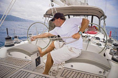 Man sailing a sailboat pulling the ropes tight.