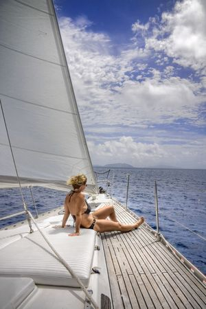 Attractive woman sitting on the front of large and luxurious sailboat sailing through the tropics. Фото со стока