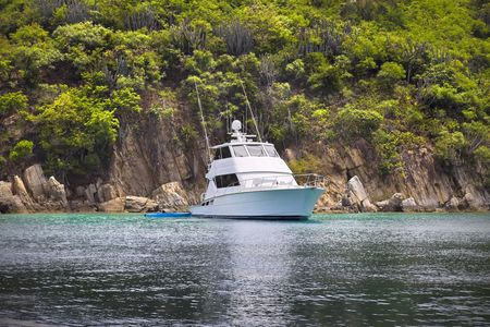 large: Large luxurious fishing boat anchored next to tropical island. Stock Photo