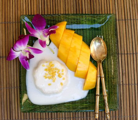Thai dessert of glutinous rice and mango with cream. photo