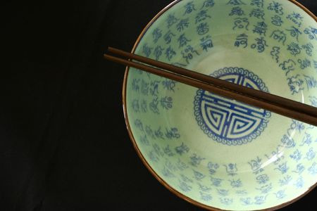 shown: Chinese bowl isolated on a blackbackground. No trademark or logo shown. Stock Photo
