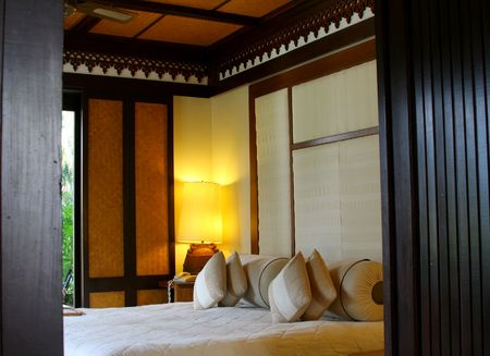 Hotel room in a tropical resort with a comforable bead and wooden flooring. Concept: Travel and vacation.