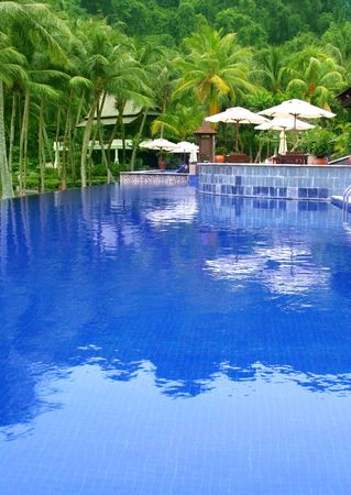 Swimming pool at a resort with blue water reflecting coconut palm trees. Water ripple not noise. Stock Photo