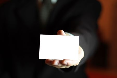 friendly competition: Business man presenting his card with copy space. Shallow DOF, focus on thumb and card.