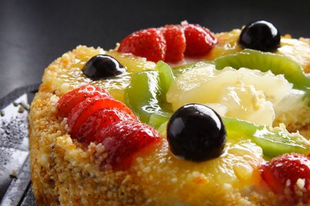 Colorful fruit cake against a dark background. Grain in background is texture of table not noise. Stock Photo - 702899