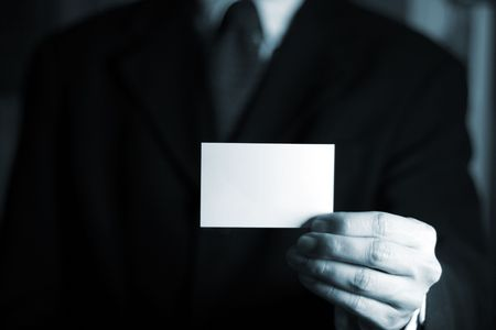 Business man presenting his card with copy space. Shot with blue filter. Stock Photo - 702344