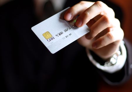 Business man presenting his credit card. Shallow DOF, focus on chip o card. Concept: Shopping and spending. photo