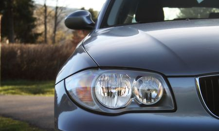Front of a car with a blurred background. Metallic paint texture on car, not noise. Focus on lights. Stock Photo