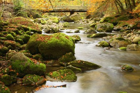 Autumn scene with flowing river taken with slow shutter speed on a tripod and lowest ISO. Stock Photo - 709971