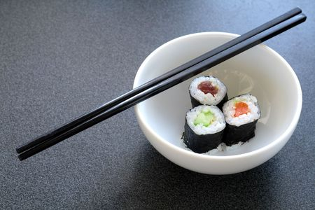 Japanese sushi (raw fish) with a pair of chopsticks. Table is textured, not noise or artifacts. photo