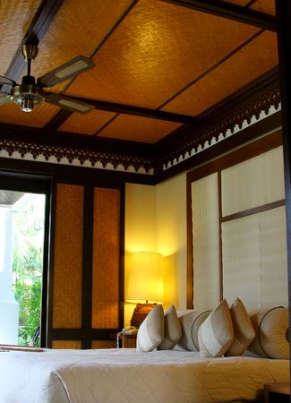 Hotel room in a tropical resort with a comforable bead and wooden flooring. Concept: Travel and vacation. photo