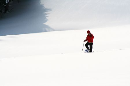 the slope: A person dressed in red ski clothes, skiing down a snow covered slope. Stock Photo