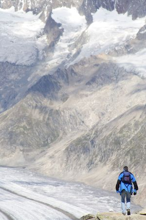Lone man climbing a mountain covered with patches of snow. Signs of global warming. Stock Photo - 726747