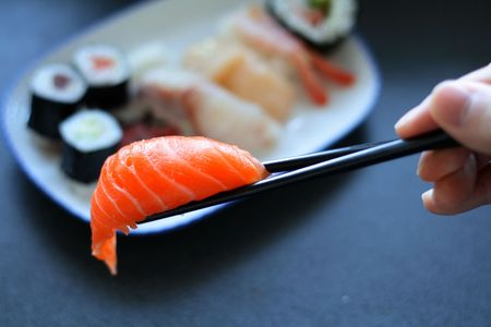 Japanese sushi (raw fish) with a pair of chopsticks. Table is textured, not noise or artifacts.