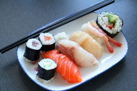 artifacts: Japanese sushi (raw fish) with a pair of chopsticks. Table is textured, not noise or artifacts.