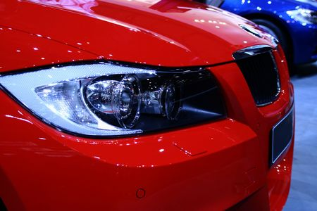 Side profile of a red car. Focus on the head lights. Stock Photo