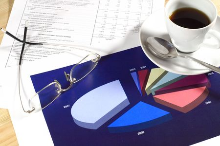 year financial statements: A cup of coffee and glasses resting on a colorful generic pie chart. Concept: Financial statement. Stock Photo