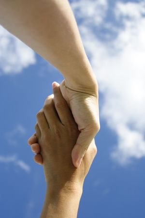 reached: A pair of hands holding or shaking each other against a blue sky. Concept: Agreeement reached or helping hand. Stock Photo