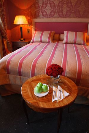 Cosy looking hotel bedroom with a vase of roses and apples on a round table. photo