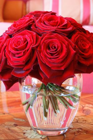 A vase full of red roses in a clear glass vase on a wooden table. photo