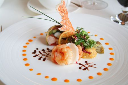 starter: Starter or Entree of a french dish with seafood mixed among salad leaves.