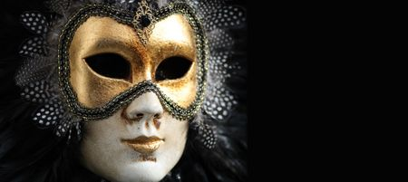 Venetian mask decorated with gold leaf and embedded with fowl feathers. photo