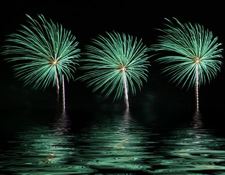 Bright and colorful fireworks display with reflection on water. photo