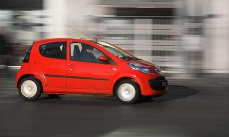 panning shot: Piccola auto rossa generico accelerazione della citt�. Panning sparato, non Sfumatura movimento