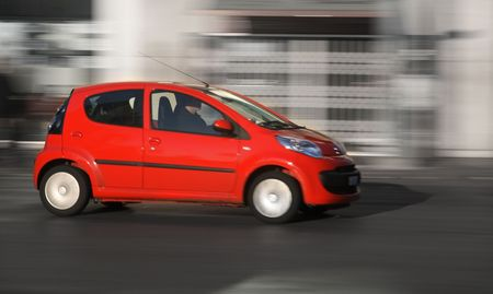 Small red generic car speeding in the city. Panning shot, not motion blur