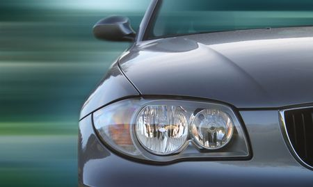 headlights: Front of a car with a blurred background. Metallic paint texture on car, not noise. Focus on lights. Stock Photo