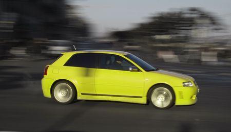 panning shot: Small yellow generic car speeding in the city. Panning shot, not motion blur